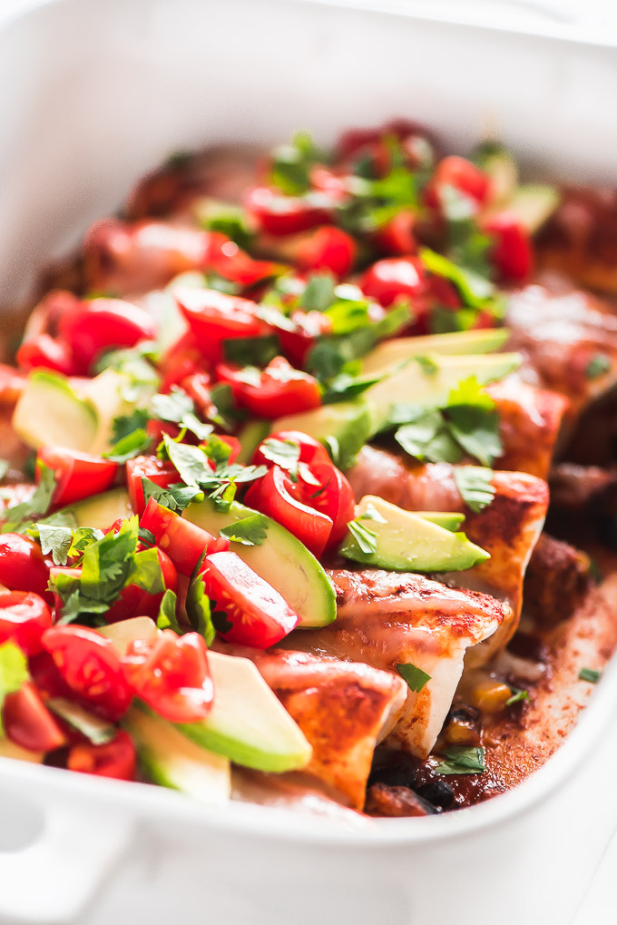 Casserole dish full of Black Bean and Sweet Potato Enchiladas topped with melted cheese, avocado slices, and diced tomatoes.