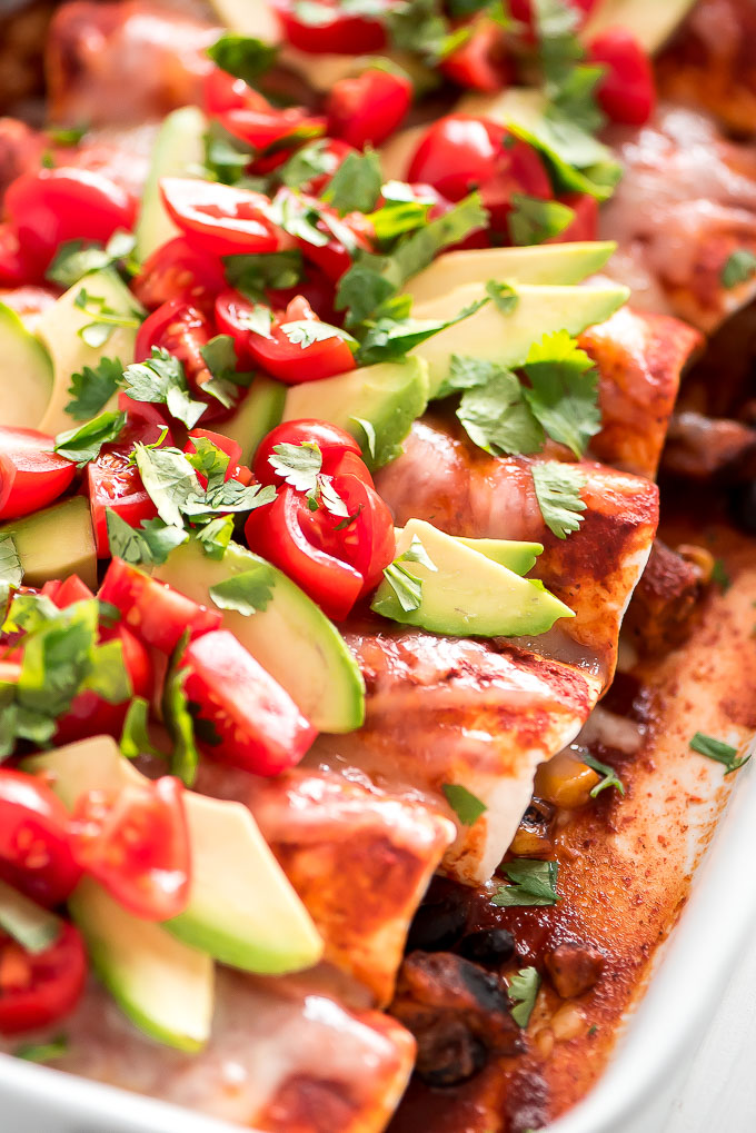 Close up of Black Bean and Sweet Potato Enchiladas topped with melted cheese, avocado slices, cilantro, and diced tomatoes.