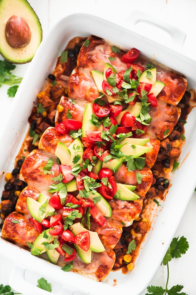 Birds eye view of a casserole dish full of Black Bean and Sweet Potato Enchiladas topped with melted cheese, avocado slices, and diced tomatoes.