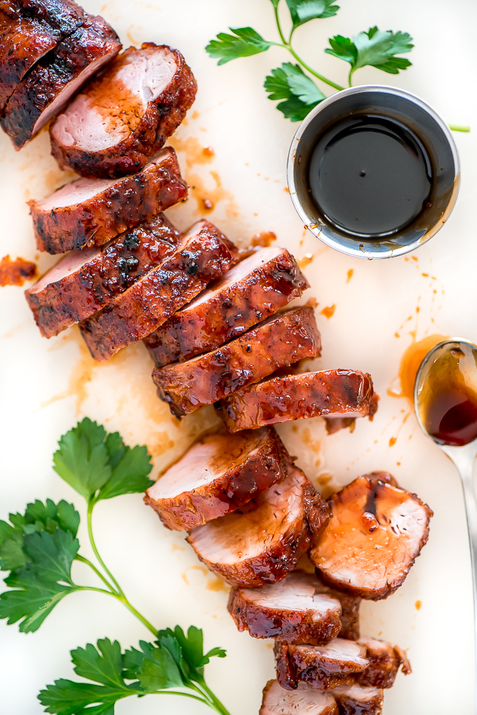 Maple glazed roasted pork tenderloin slices up on a white cutting board.