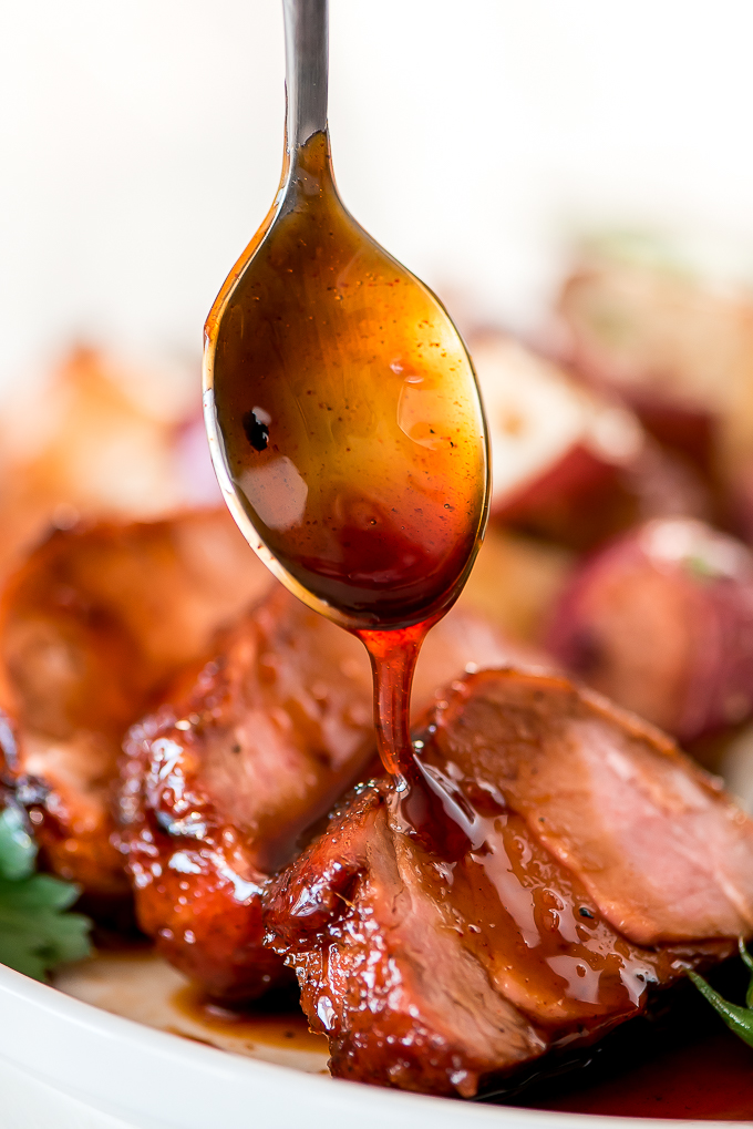 Close up of drizzling maple glaze over roasted pork tenderloin slices.