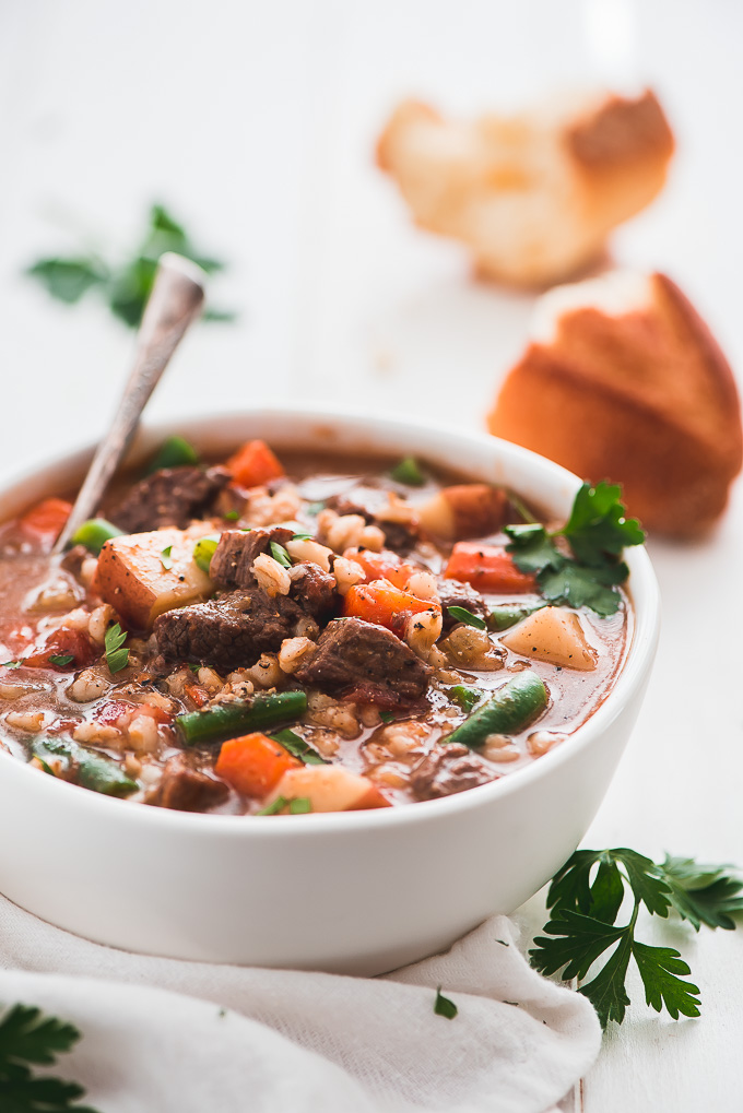 A bowl of Instant Pot Beef and Barley Soup garnished with black pepper and fresh parsley.