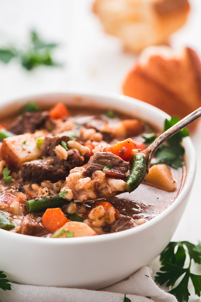 Close up of a spoonful of Beef and Barley Soup full of beef, barley, carrots, green beans, and garnished with parsley.