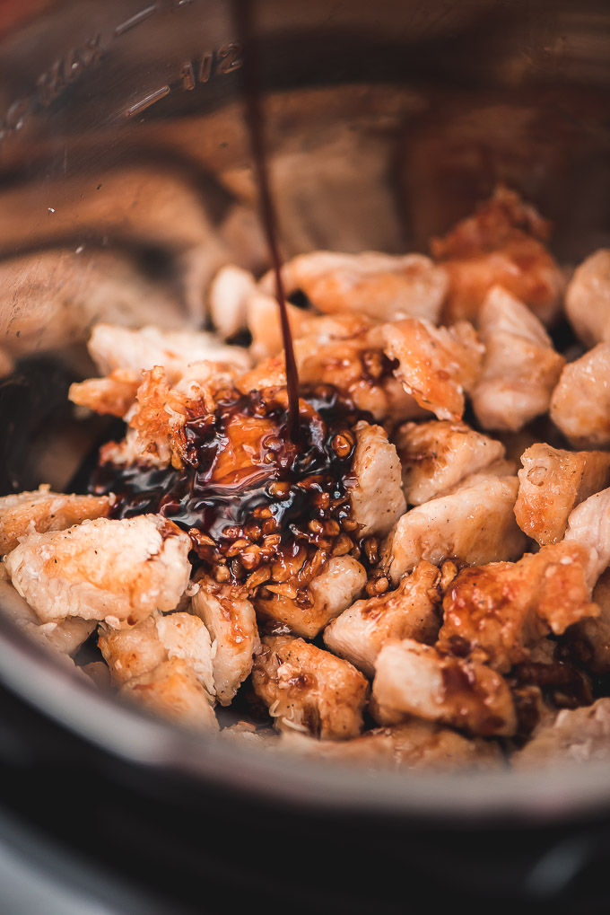 Pouring honey garlic sauce over chicken in the Instant Pot pressure cooker.