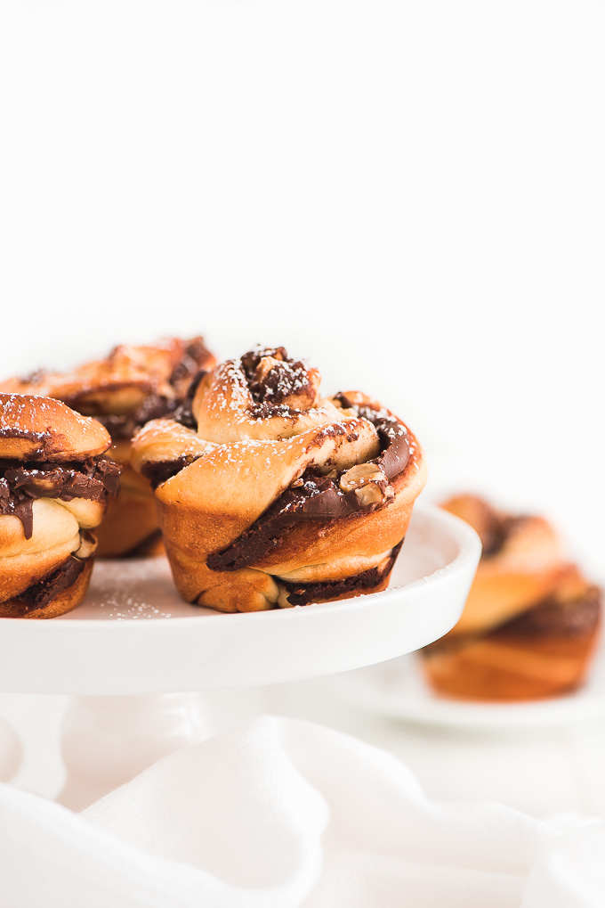 Nutella Twist pastries dusted with powdered sugar on top of a cake stand.