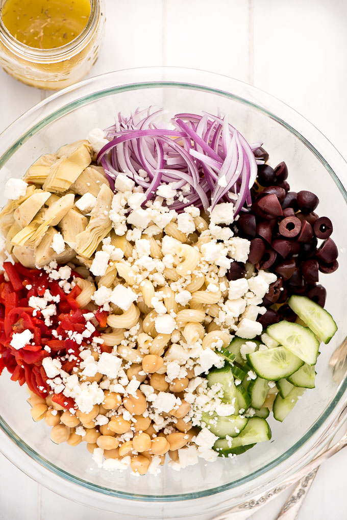 Large mixing bowl of Mediterranean Pasta Salad full of cavatappi noodles, kalamata olives, cucumbers, red onions, artichoke hearts, and pimientos.