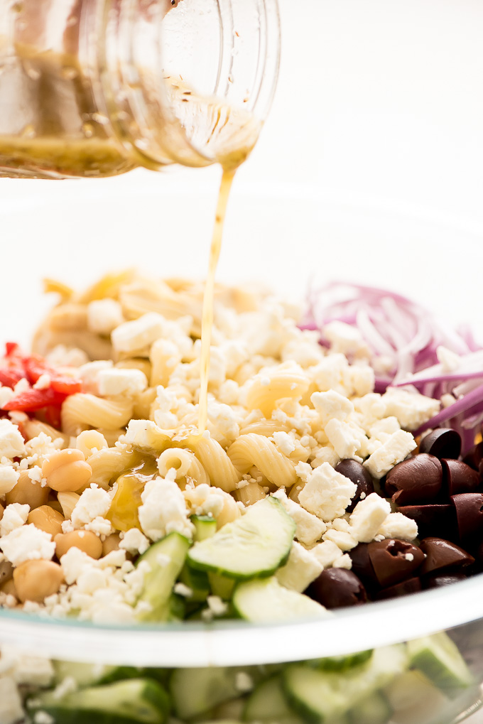 Pouring Greek dressing over the top of Mediterranean Salad.