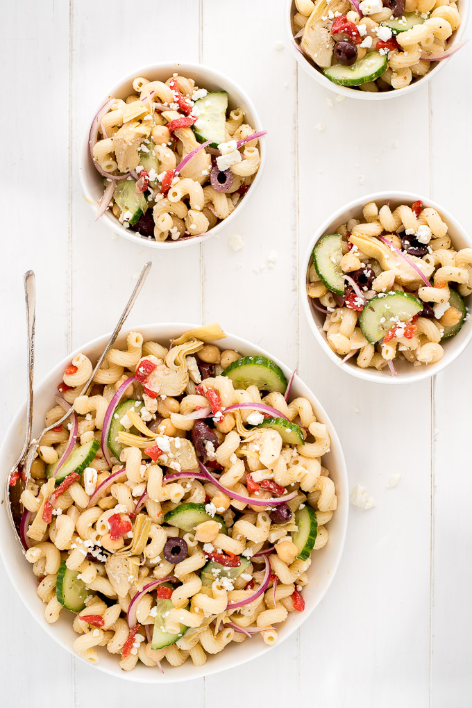 Table top with one large bowl and three little bowls of Mediterranean Pasta Salad.