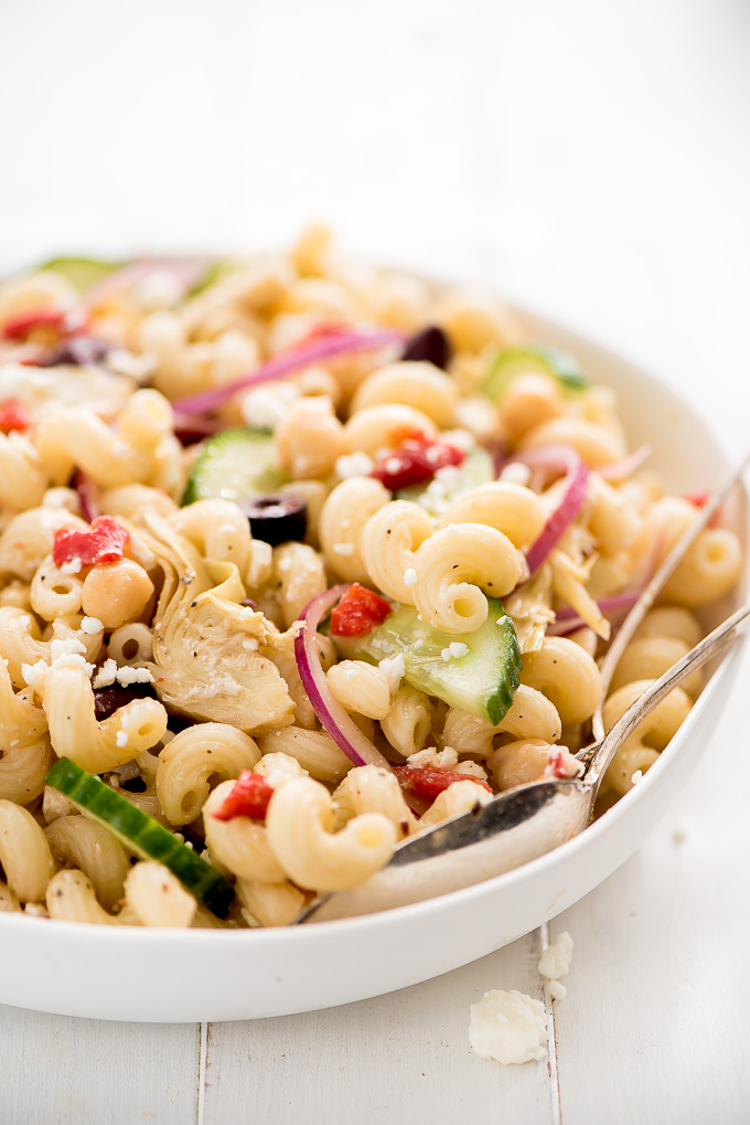Bowl of Mediterranean Pasta Salad full of cavatappi noodles, kalamata olives, cucumbers, red onions, artichoke hearts, and pimientos.