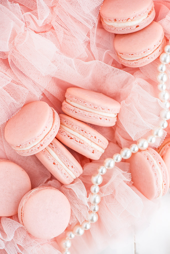 Pink French Macarons arranged on top of a tutu and a strand of pearls.