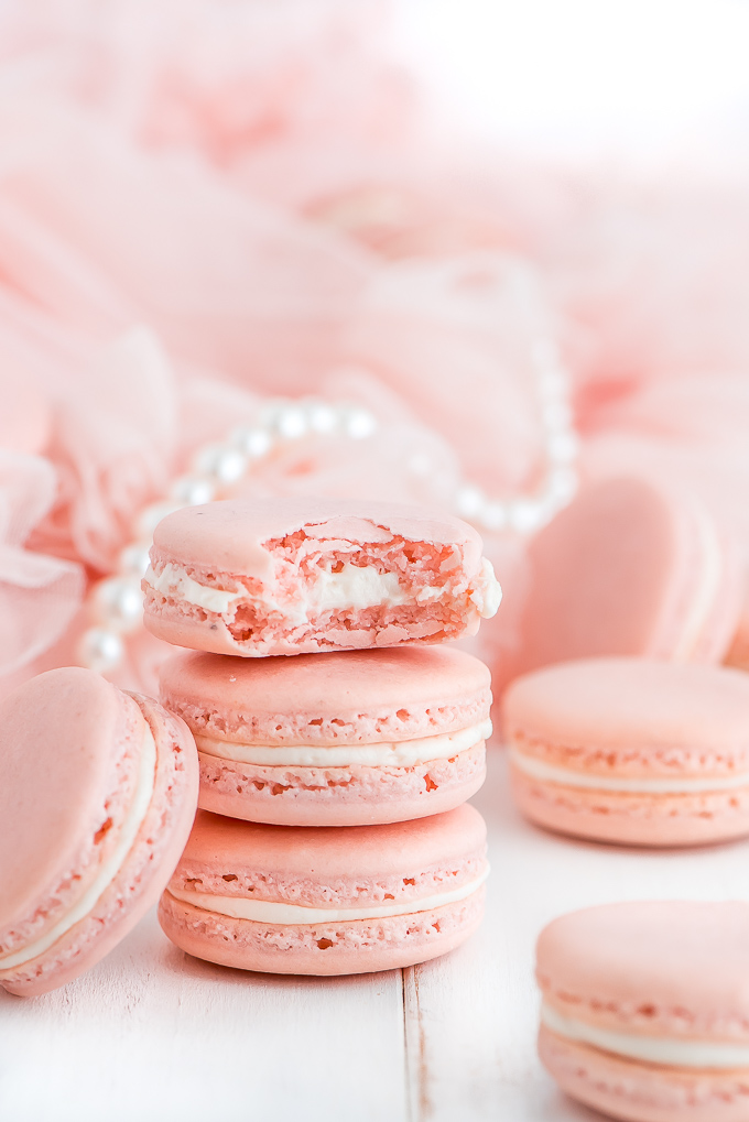 Pink French Macarons stacked up with one with a bite taken out.