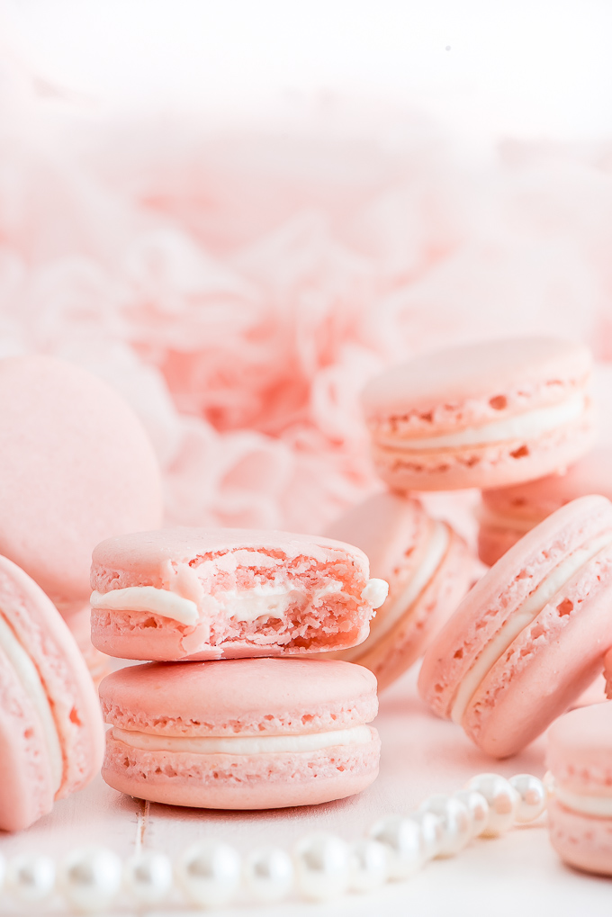 Pink French Macarons stacked with one with a bite taken out.