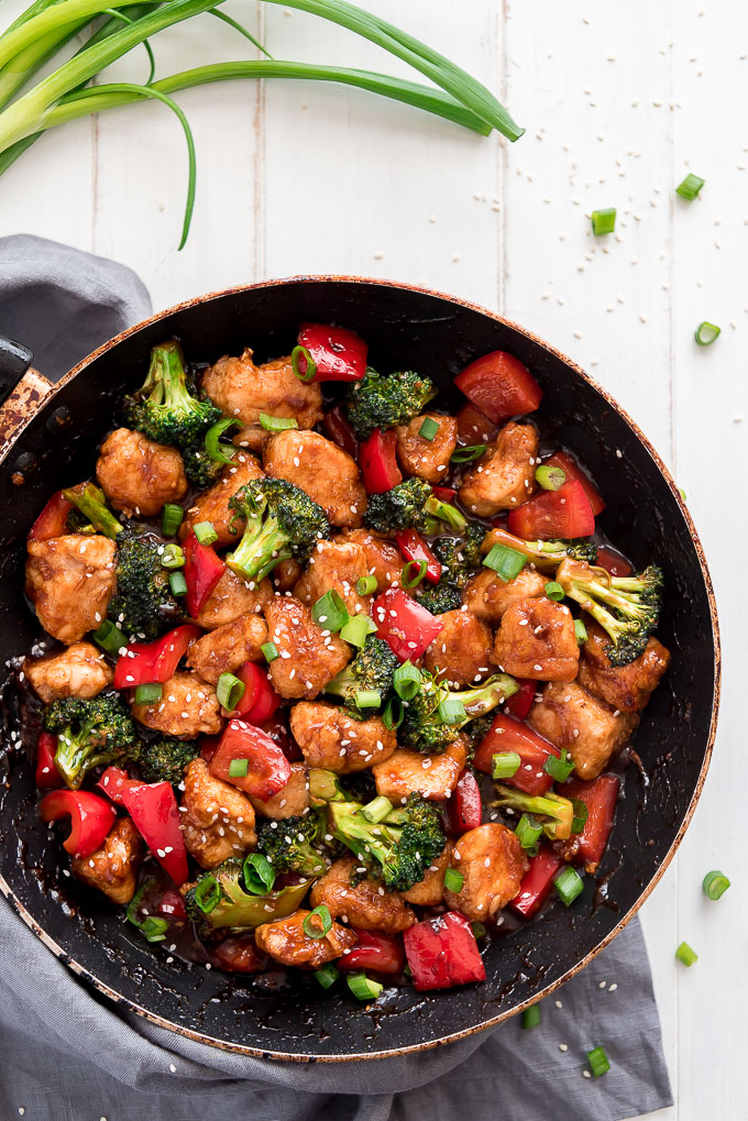 General Tso's Chicken in a skillet with red bell peppers, broccoli, sesame seeds and green onions.