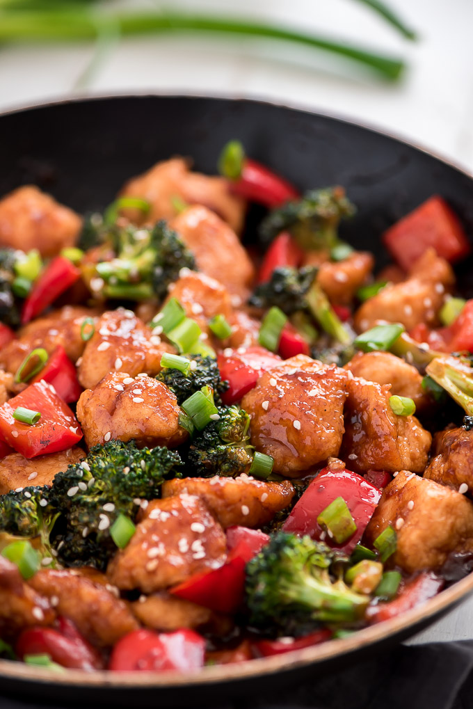 General Tso Chicken in a skillet with red bell peppers, broccoli, and green onions.