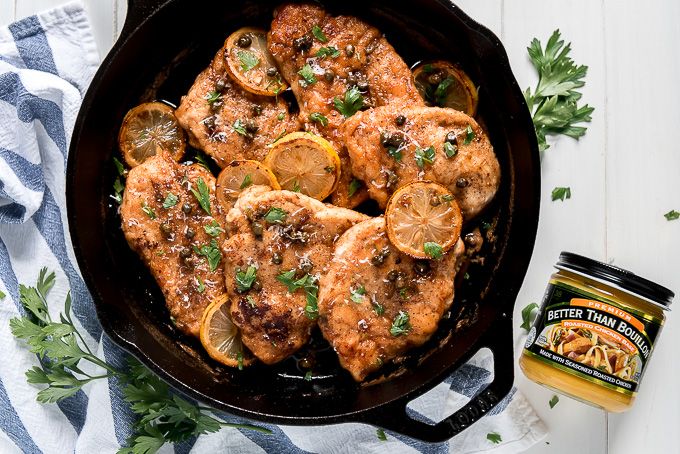 Chicken Piccata in a skillet topped with lemon slices.
