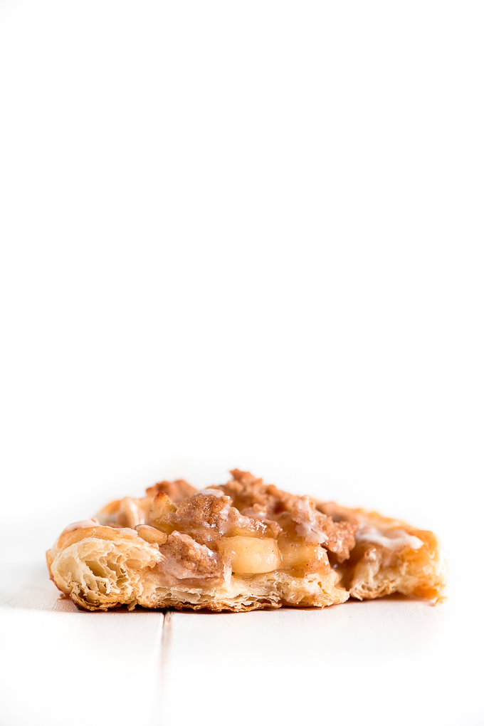 Half of an Apple Danish showing the flaky puff pastry, apple pie filling, streusel topping, and glaze.