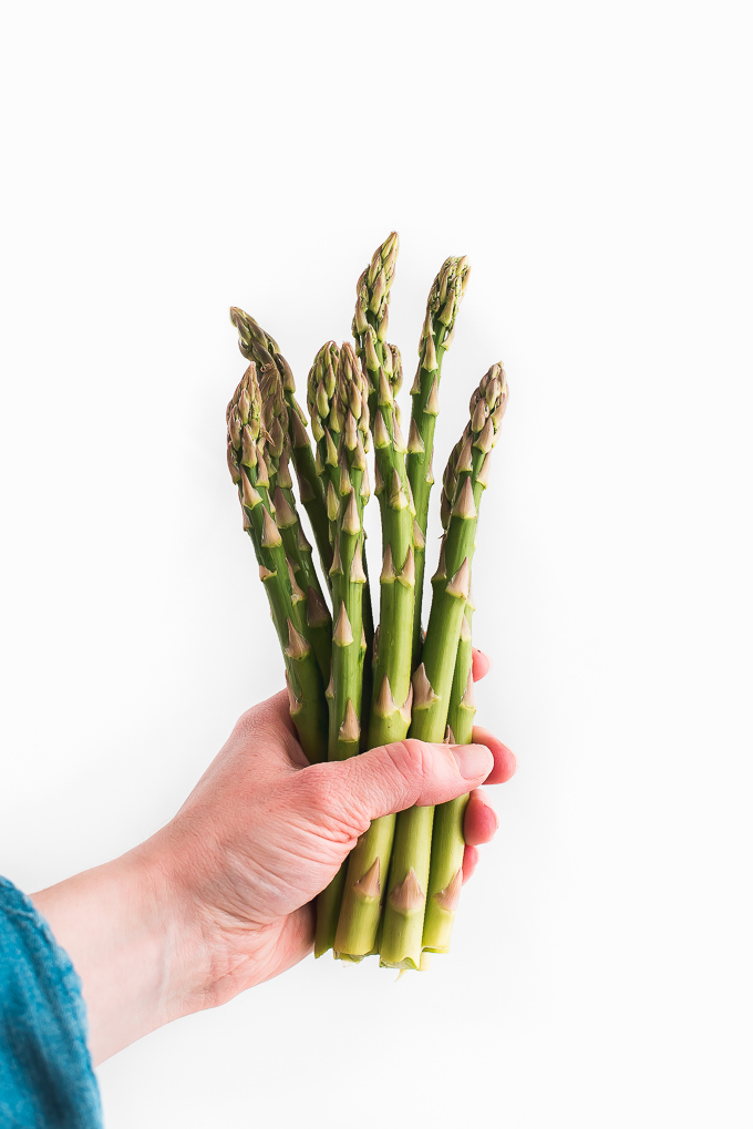 Holding a bunch of asparagus spears.