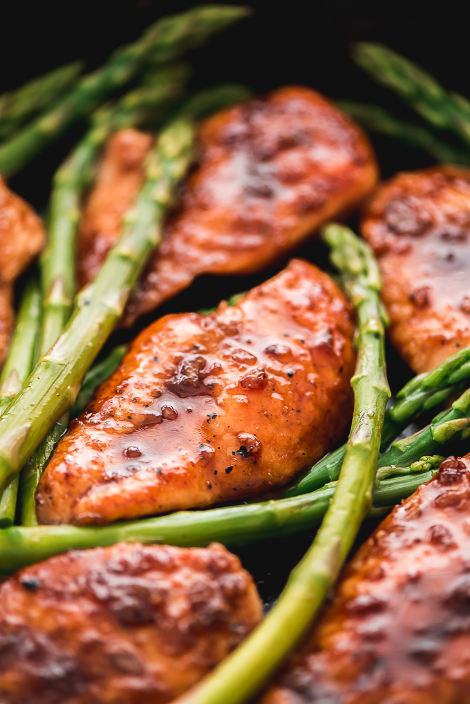 Closeup of Honey Garlic Chicken & Asparagus in a cast iron skillet. Chicken is glazed with the sweet garlic sauce.