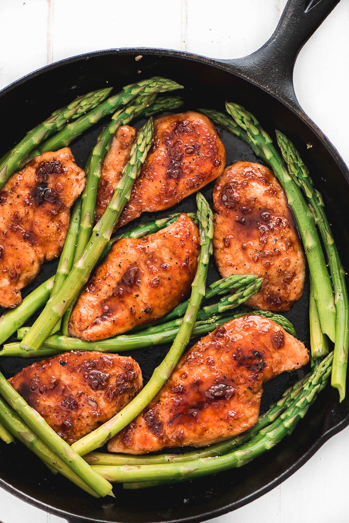 Top view of Honey Garlic Chicken & Asparagus in a cast iron skillet.