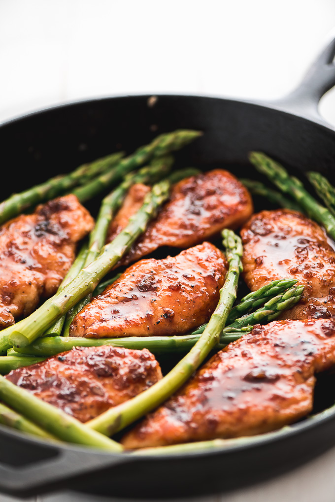 Honey Garlic Chicken glazed with sweet and savory sauce, surrounded by asparagus spears.