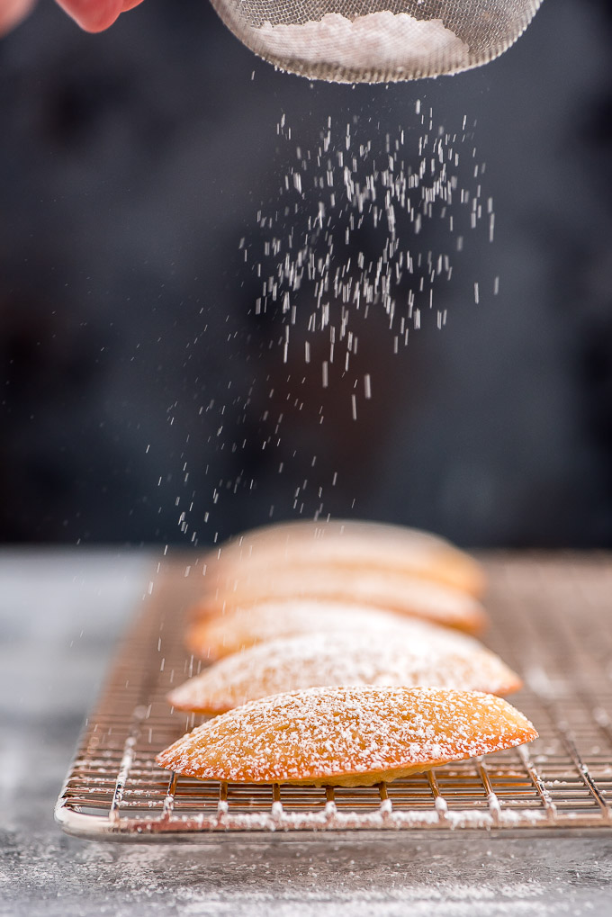 Dusting Madeleines with powdered sugar.