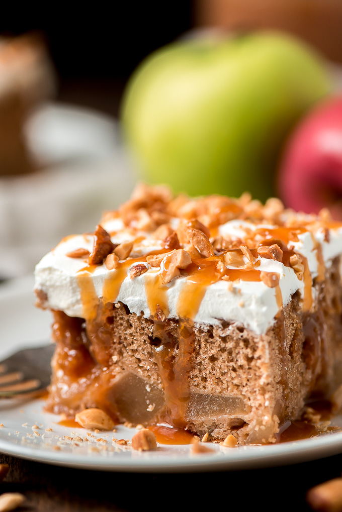 Close up of a slice of Caramel Apple Poke Cake drizzled with caramel sauce and sprinkled with roasted peanuts.