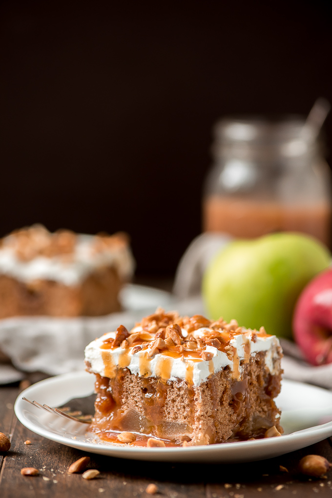 A square slice of Caramel Apple Cake topped with whipped cream, drizzled with caramel sauce, and sprinkled with peanuts.