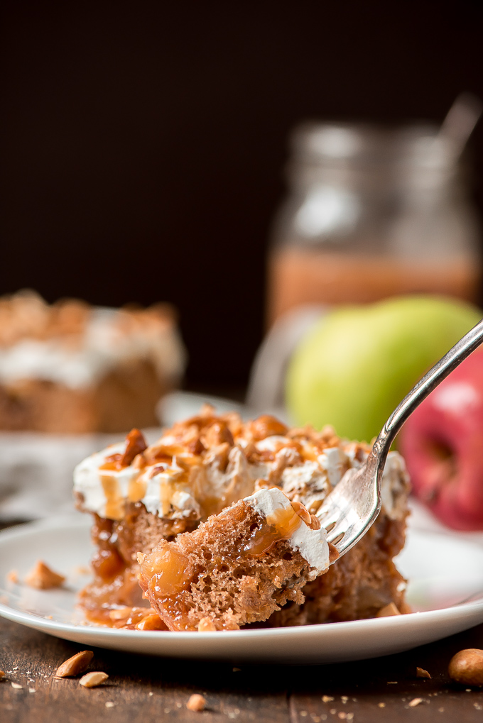 Close up of a fork full bite of Caramel Apple Poke Cake showing the caramel sauce, apple pieces, and moist spice cake.
