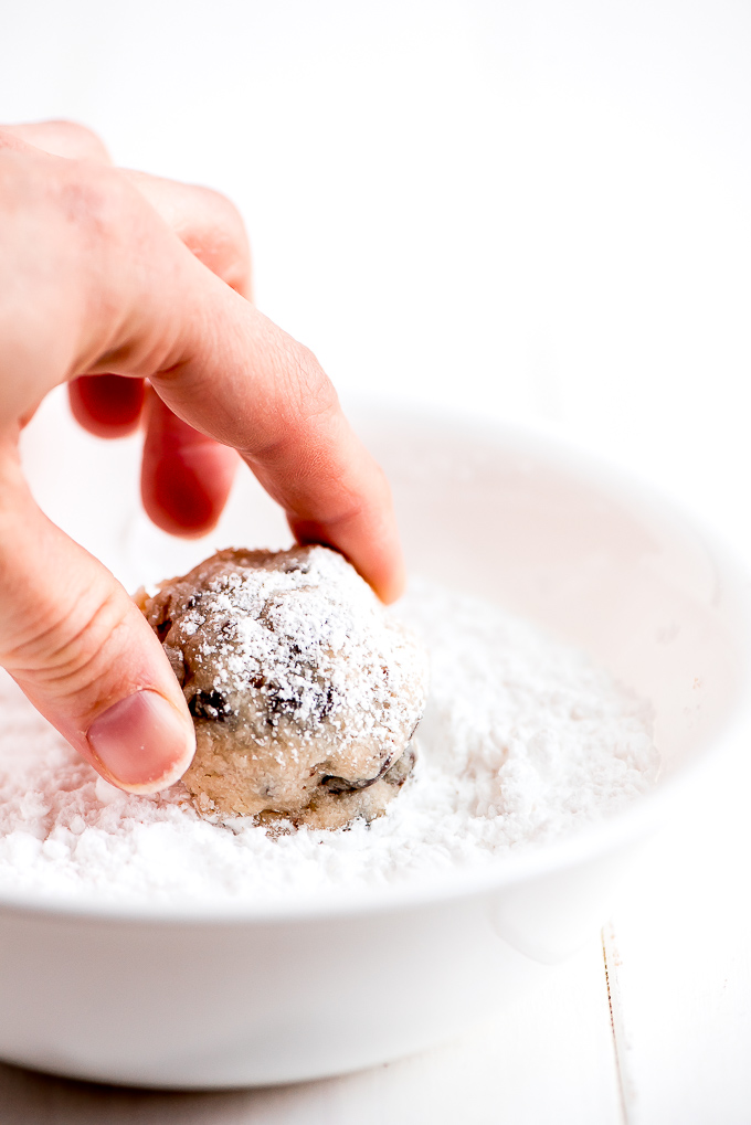 Rolling Chocolate Chip Snow Ball Cookie in a bowl of powdered sugar