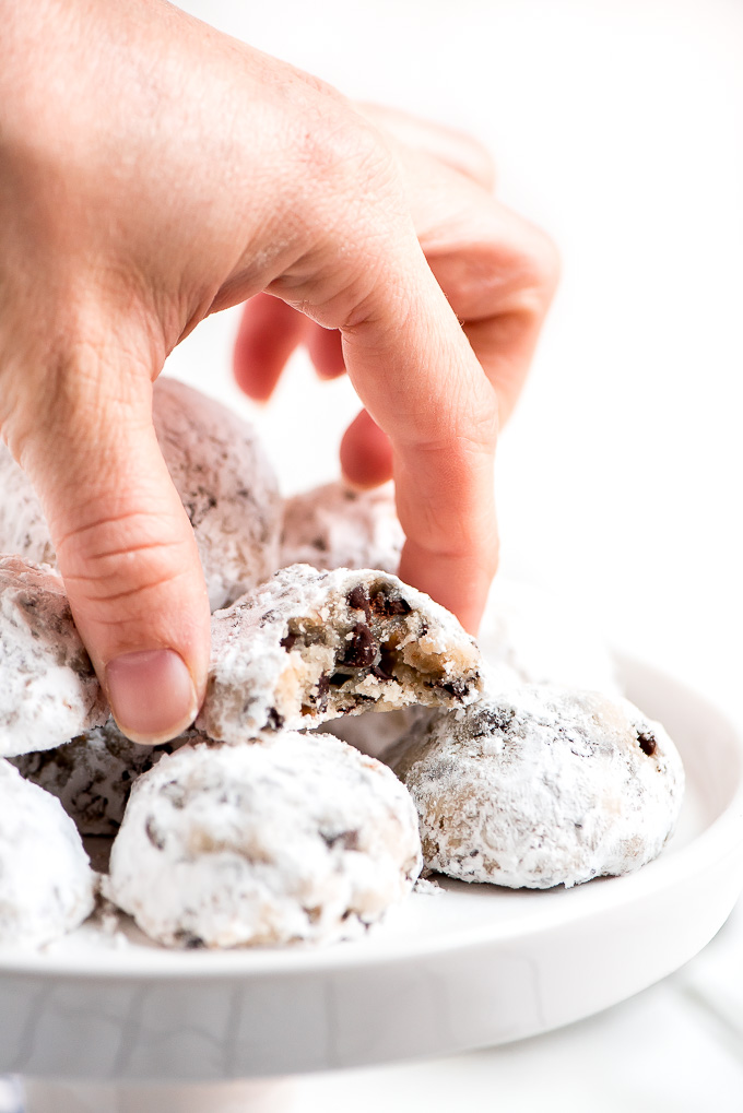 Picking up a Snowball Cookie from a cake stand platter of cookies.