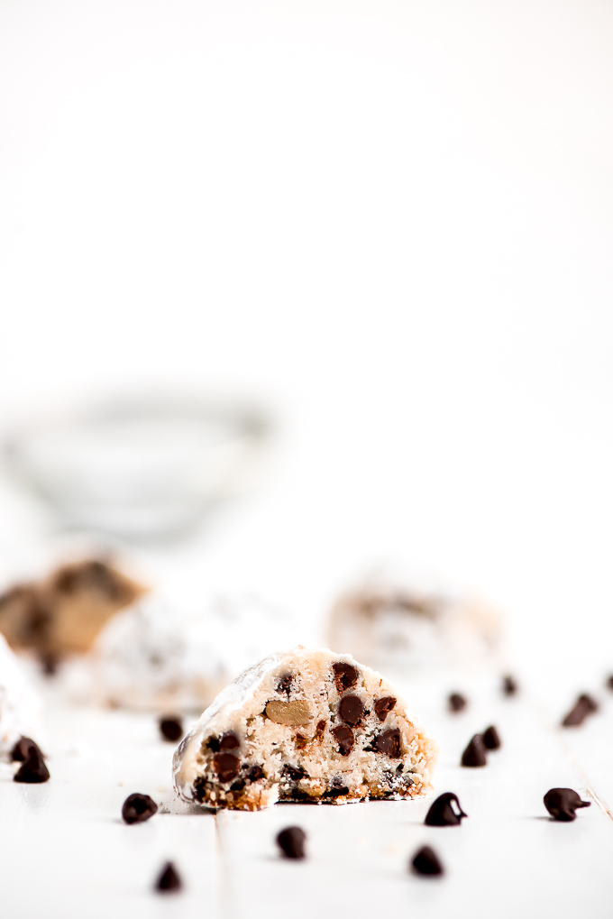 Half of a Chocolate Chip Snowball Cookie with chocolate chips scattered around.