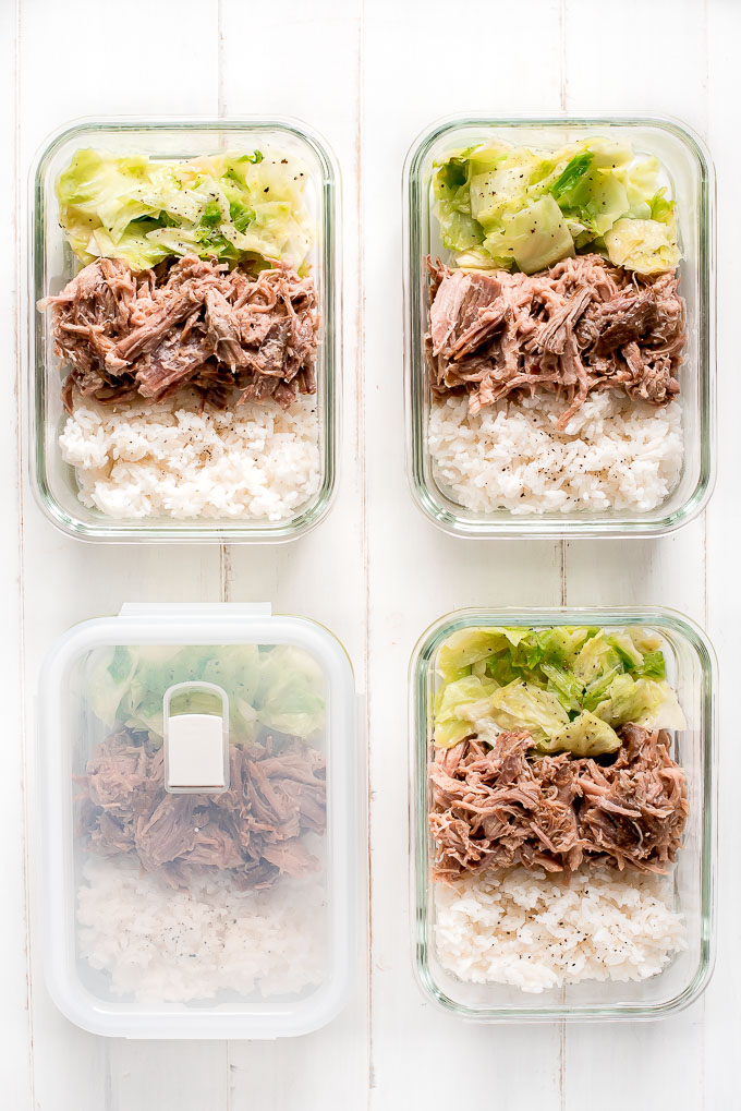 Meal Prep Instant Pot Kaula Pork in 4 glass containers along with rice and cooked cabbage.