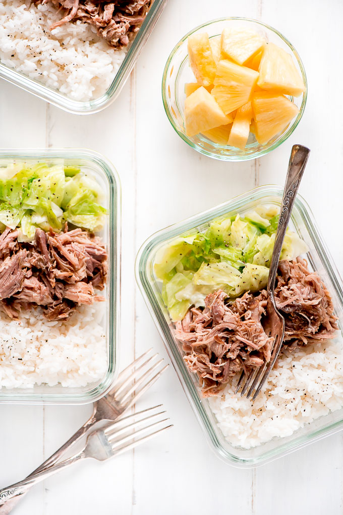 Meal Prep Kaula Pork in glass containers along with rice, cooked cabbage and a side of pineapple.