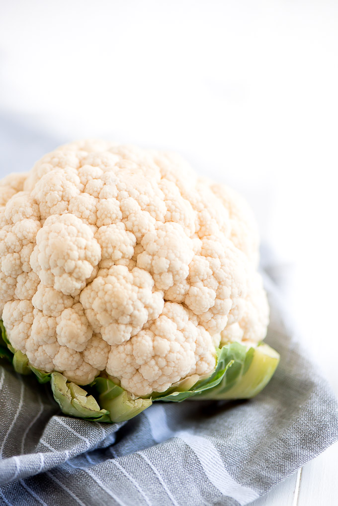 A head of cauliflower on a gray towel.