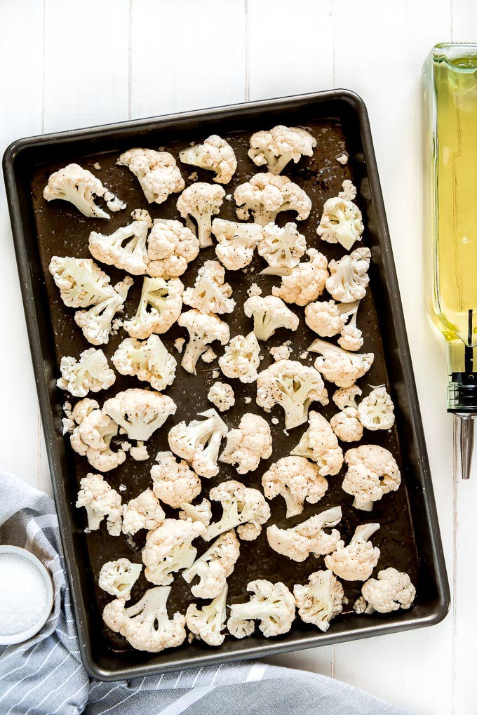 Raw cauliflower on a baking sheet, drizzled with oil, and sprinkled with salt and pepper.