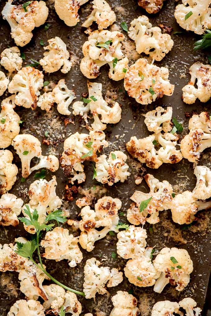 Close-up of Parmesan Roasted Cauliflower sprinkled with parsley, salt, and pepper.