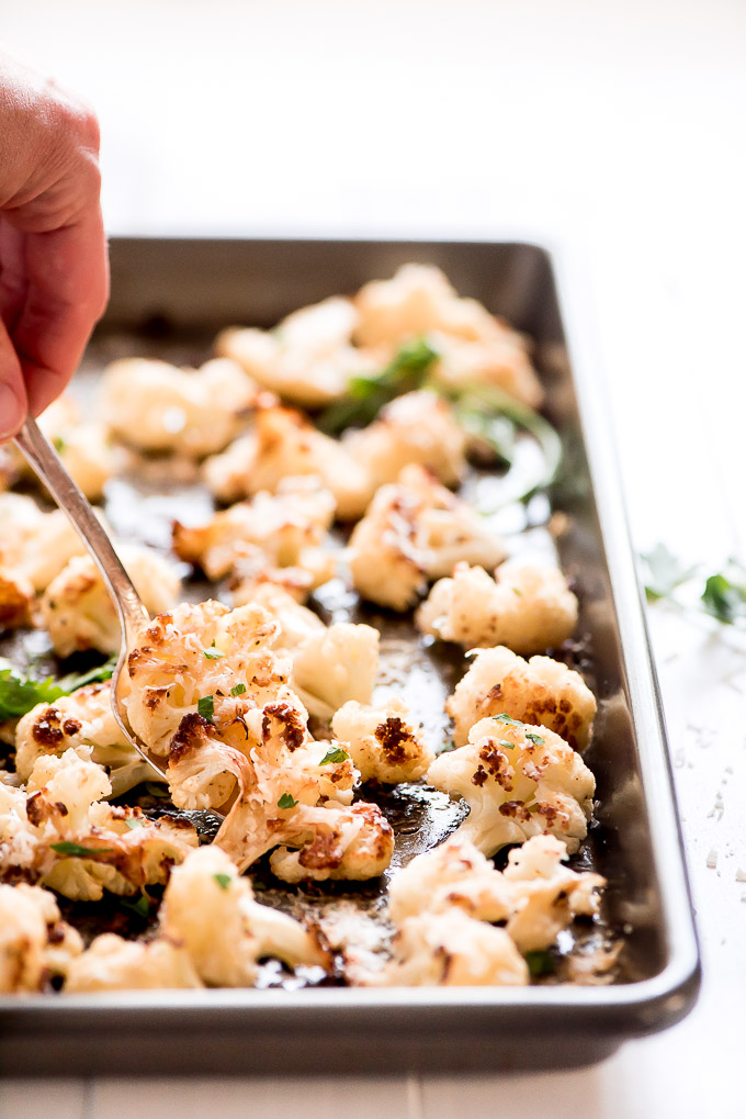 Close-up of spooning Roasted Cauliflower off a pan.