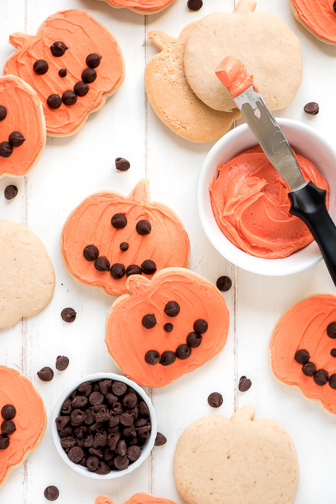 Table covered with the best soft sugar cookies shaped as pumpkins, frosting with orange buttercream frosting and topped with chocolate chip smiley faces.