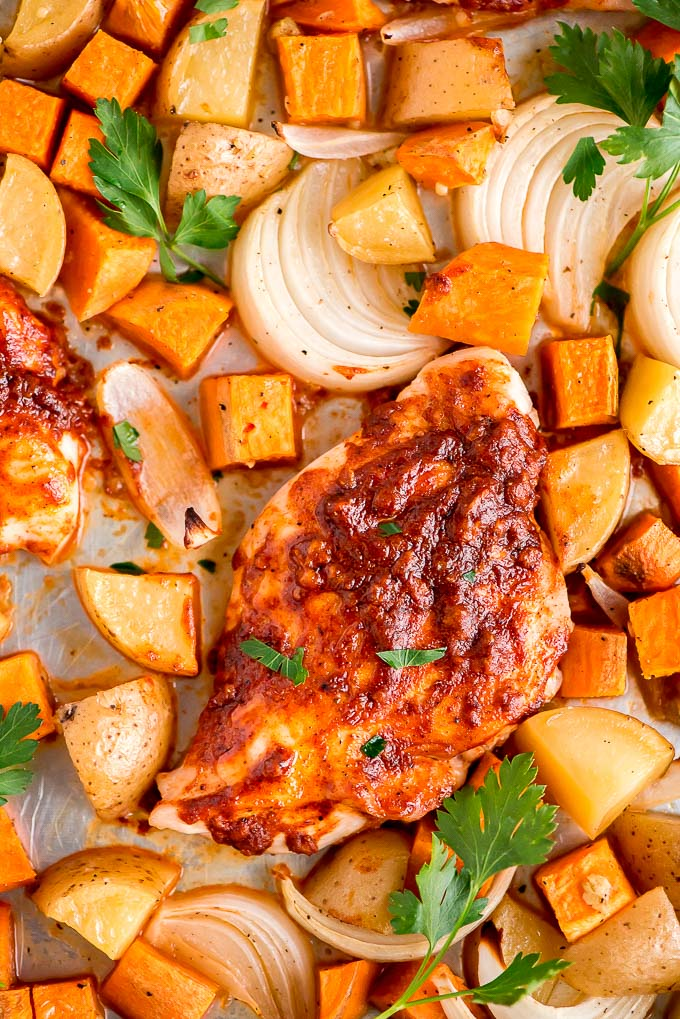 Close up top view of Sheet Pan Paprika Chicken with onions, sweet potatoes, and yukon potatoes.