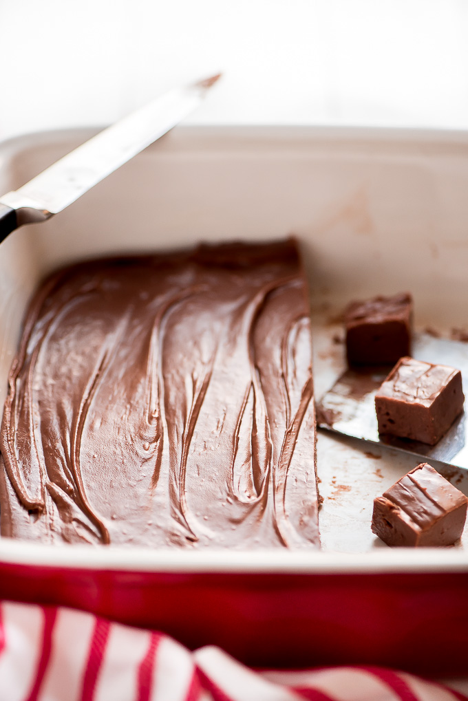 Easy Chocolate Fudge in a pan with some pieces already cut.
