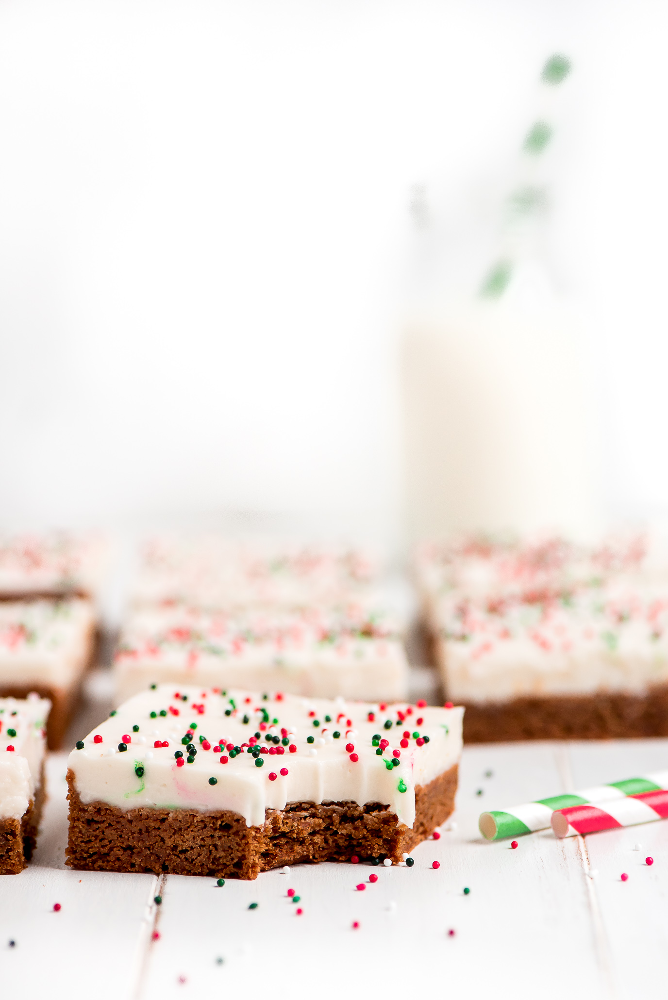 Gingerbread Sugar Cookie Bars frosted with cream cheese frosting and sprinkled with red, white, and green sprinkles.