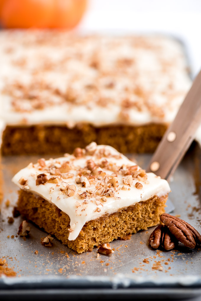 A piece of Pumpkin Sheet Cake topped with cream cheese frosting and chopped pecans on a sheet pan, ready to be lifted out with a spatula.
