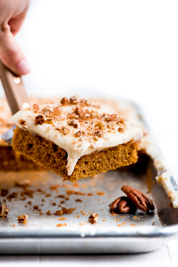 Lifting a piece of Pumpkin Sheet Cake with cream cheese frosting and chopped pecans from a sheet pan.