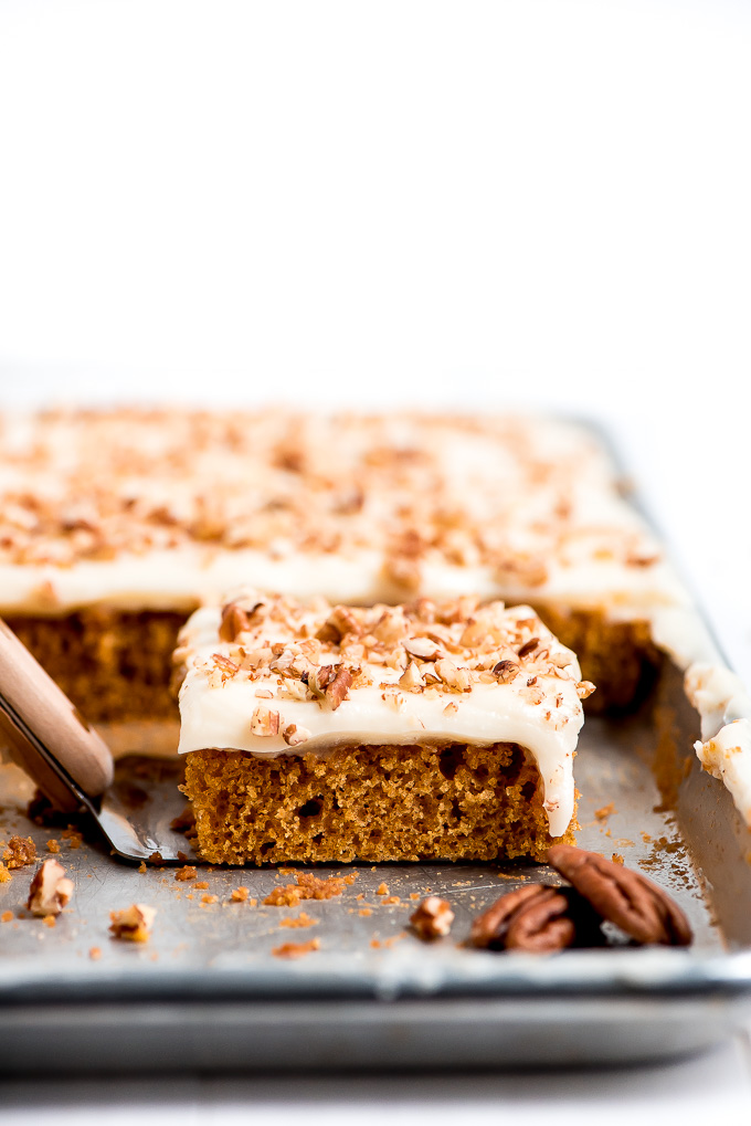 A square piece of Pumpkin Sheet Cake topped with cream cheese frosting and pecans on a pan.