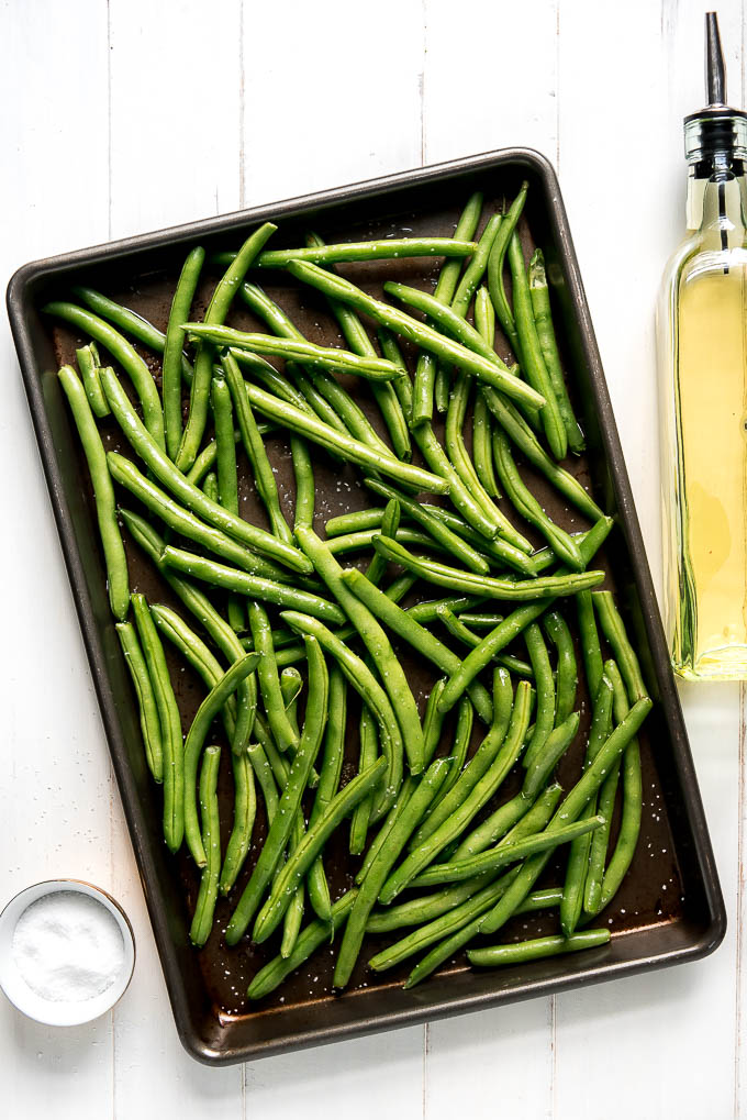 Raw green beans on a baking sheet drizzled with olive oil and sprinkled with salt.