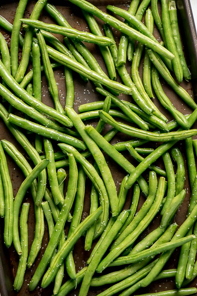 Close up photo of raw green beans tossed in olive oil and kosher salt.