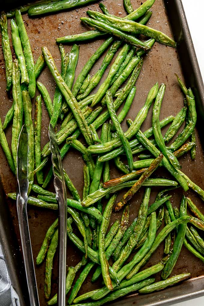 Roasted Green Beans on a baking sheet, slightly shriveled and browned.