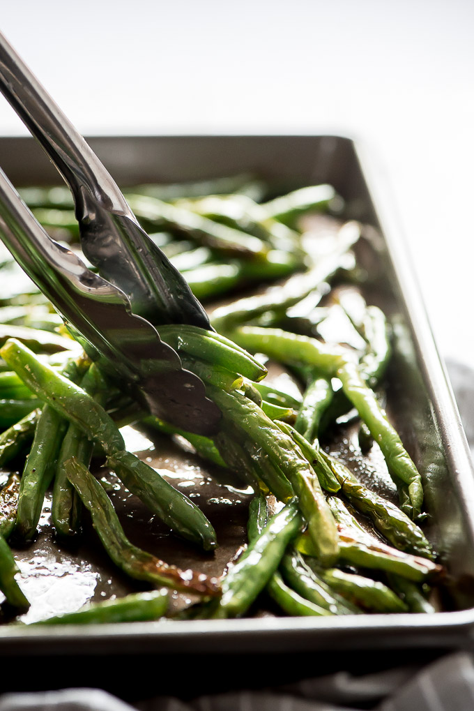 Picking up Roasted Green Beans with tongs from a sheet pan.