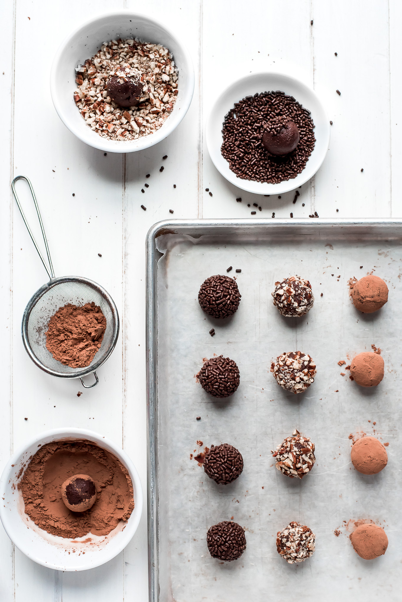 Chocolate Truffles on a baking sheet with bowls of sprinkles, chopped pecans, and cocoa powder for rolling them in.