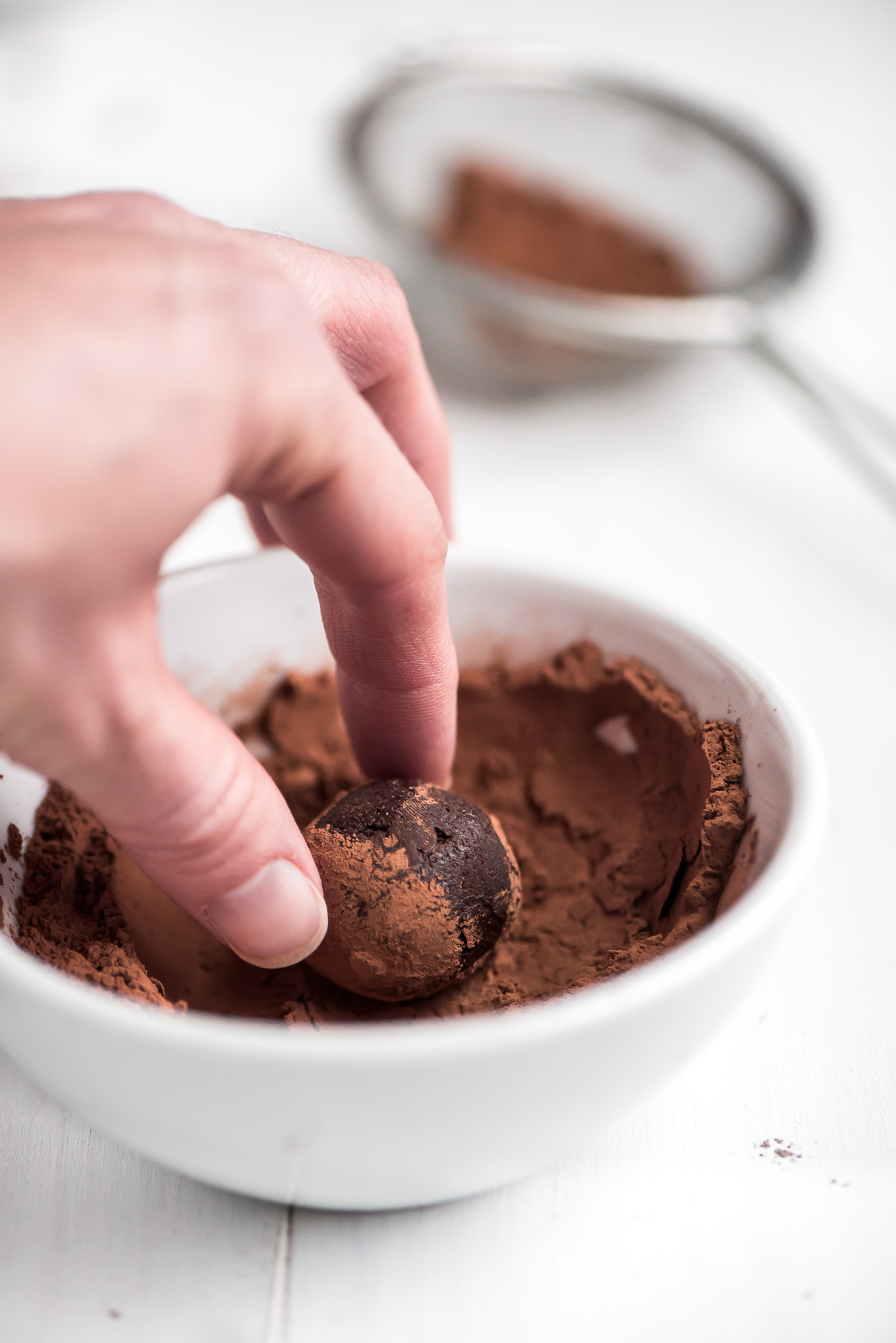 Making a chocolate truffle by rolling a bowl of ganache in a small bowl of cocoa powder.